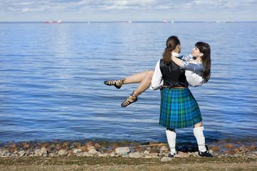Man in scottish costume holding woman near the sea