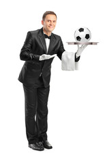 Butler with bow tie holding a tray with a football on it