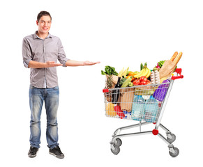 Man gesturing and shopping cart full of groceries