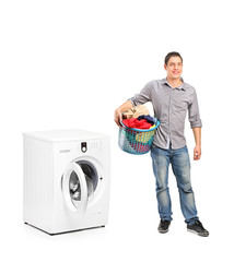 Smiling male holding a laundry basket and a washing machine