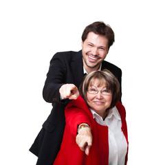 junger Geschäftsmann und ältere Frau zeigen in die Kamera