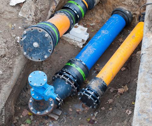Leinwandbild Motiv Gas- und Wasserrohre in einer Baugrube
