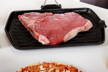 Uncooked steak on grill.