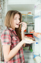 girl eating  meat from  refrigerator