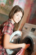 girl putting clothes in to washing machine