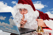 Santa Claus with bell, at the laptop