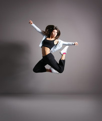 Young and sexy modern dancer over grey background