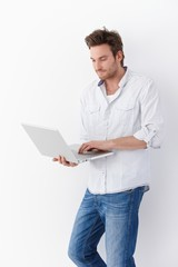 Young man using laptop standing smiling