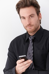 Goodlooking businessman holding mobile phone