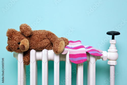 Leinwanddruck Bild Teddy bear and gloves on an old radiator
