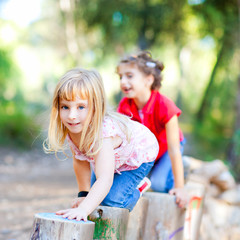 kid girls playing on trunks in forest nature