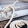 White mooring rope tied around steel anchor on boat or ship.