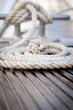 Mooring rope with a knotted end tied around a cleat on a pier.