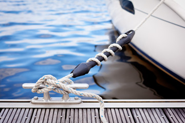 A white yacht moored with a line tied around a metal fixing