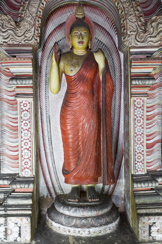 standing buddha in the cave of dambulla, sri lanka