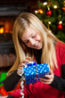 girl opening gift on christmas eve