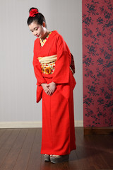Oriental model in red Japanese kimono bowing
