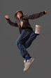 boy in a jump simulates a dance element on a gray background