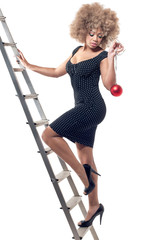 Young beautiful woman on ladder holding a Christmas ball