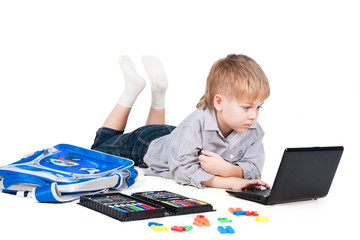 little schoolboy learning with laptop isolated on white