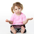 Clueless looking little girl sitting on the floor with touchpad