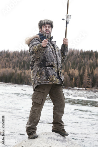 A fisherman on the river in winter