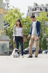 Woman holding a puppy on leash with a man standing beside her, Paris, Ile-de-France, France