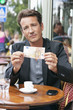 Man showing a 50 Euro banknote in a restaurant, Paris, Ile-de-France, France