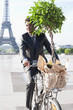 Businessman carrying a plant on a bicycle with the Eiffel Tower in the background, Paris, Ile-de-France, France