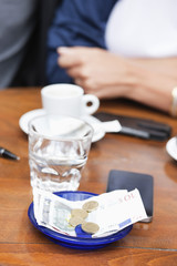 Euro banknotes and coins with bill on a table in a restaurant, Paris, Ile-de-France, France