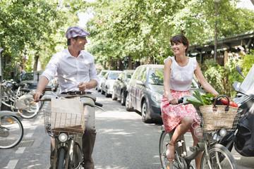 Couple carrying vegetables on bicycles, Paris, Ile-de-France, France