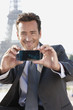 Businessman taking a picture of himself with the Eiffel Tower in the background, Paris, Ile-de-France, France