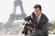 Businessman using a digital tablet with the Eiffel Tower in the background, Paris, Ile-de-France, France