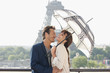 Couple under an umbrella with the Eiffel Tower in the background, Paris, Ile-de-France, France
