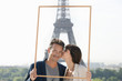 Couple framing their dream vacation with Eiffel Tower in the background, Paris, Ile-de-France, France