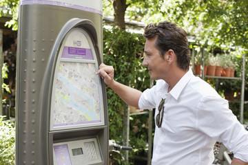 Man looking a map in a ticket machine, Paris, Ile-de-France, France