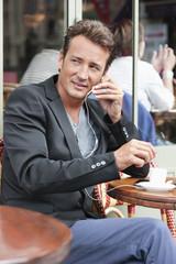 Man talking on a mobile phone in a restaurant, Paris, Ile-de-France, France