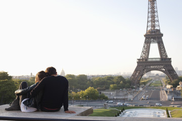 Couple sitting together with the Eiffel Tower in the background, Jardins du Trocadero, Paris, Ile-de-France, France