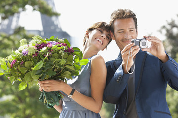 Woman holding a bouquet of flowers and man showing pictures in a digital camera with the Eiffel Tower in the background, Paris, Ile-de-France, France
