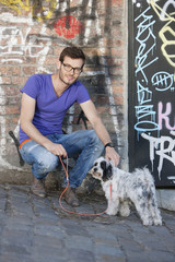 Man with a puppy in front of a graffiti wall, Paris, Ile-de-France, France