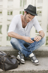 Man sitting on the ledge of a canal and listening to music with an MP3 player, Paris, Ile-de-France, France