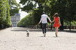 Couple running in a garden with a puppy, Terrasse De l'Orangerie, Jardin des Tuileries, Paris, Ile-de-France, France