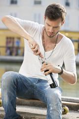 Man opening a wine bottle with a corkscrew, Paris, Ile-de-France, France