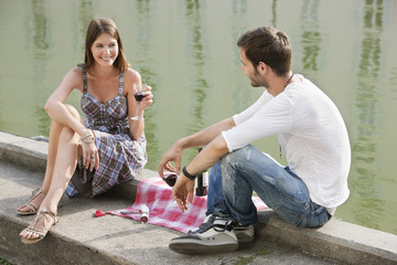 Couple drinking red wine at the ledge of a canal, Paris, Ile-de-France, France