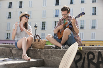 Man playing a guitar with a woman clapping and smiling, Canal St Martin, Paris, Ile-de-France, France