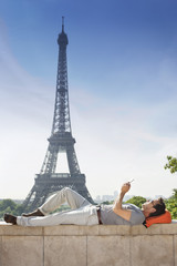 Man lying on a stone wall with the Eiffel Tower in the background, Paris, Ile-de-France, France