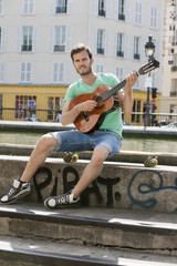 Man playing a guitar, Canal St Martin, Paris, Ile-de-France, France