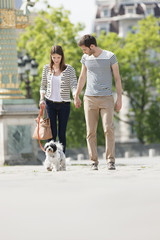 Couple walking with a puppy, Paris, Ile-de-France, France