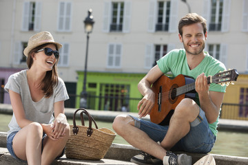 Man playing a guitar with a woman smiling, Canal St Martin, Paris, Ile-de-France, France