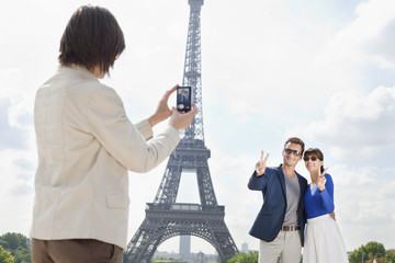 Woman taking a picture of couple with the Eiffel Tower in the background, Paris, Ile-de-France, France